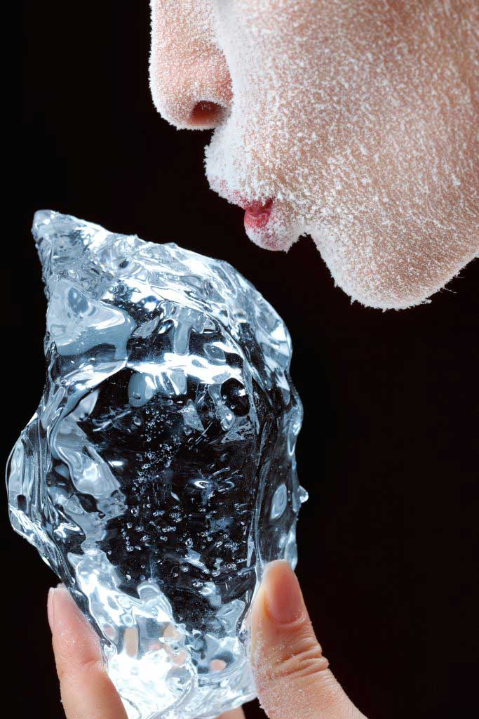 Frosted or frozen female Caucasian face and hand holding piece of ice.